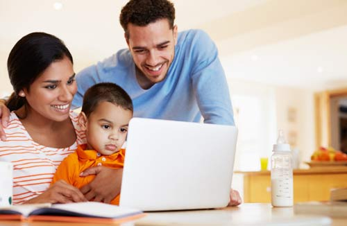 Husband, wife and child looking at their laptop
